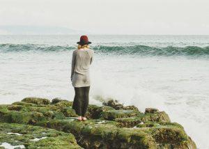 Eine Frau, die von hinten zu sehen ist, blickt auf ein Meer.