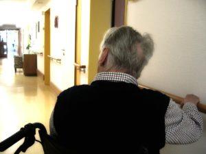 Älterer Mann im Rollstuhl, von hinten.