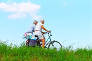 Älteres Paar fährt mit Fahrrädern über eine Wiese.