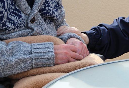 Älterer Mann sitzt im Rollstuhl, jemansd hält seine Hand. Zu sehen sind nur die Hände.