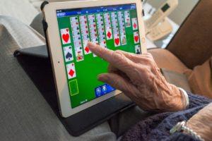 Älterer Mann spielt auf einem Tablet ein Kartenspiel, zu sehen sind das Tablet und eine Hand.