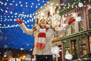 Junge Frau lacht auf weihnachtlich dekorierter Straße.
