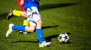 Zwei Fußballspieler kämpfen um den Ball, zu sehen sind nur die Beine.