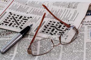 Zeitung mit Kreuzworträtsel, darauf liegen eine Brille und ein Kugelschreiber.