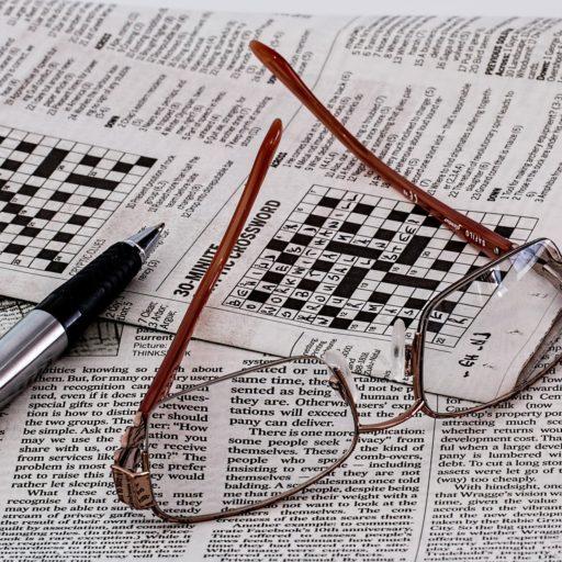 Zeitung mit Kreuzworträtsel. Darauf liegen eine Brille und ein Kugelschreiber.