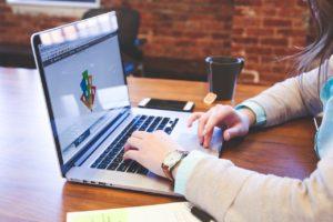 Frau arbeitet an Laptop, zu sehe nsind nur ihre Hände.