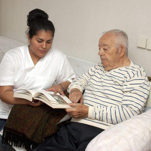 Altenpflegerin blättert mit älterem Mann in einem Buch.