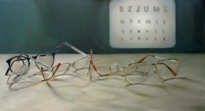 Brillen auf einem Tisch, an der Wand dahinter eine Optiker-Testtafel mit Buchstaben.