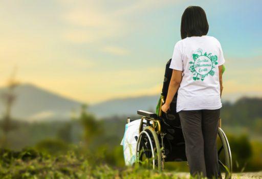 Frau schiebt eine Person im Rollstuhl
