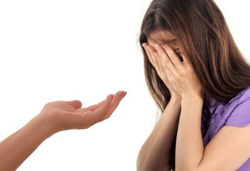Frau schlägt die Hände vors Gesicht, jemand reicht ihr eine Hand.
