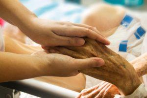 Zwei Hände umfassen die Hand eines alten Menschen.