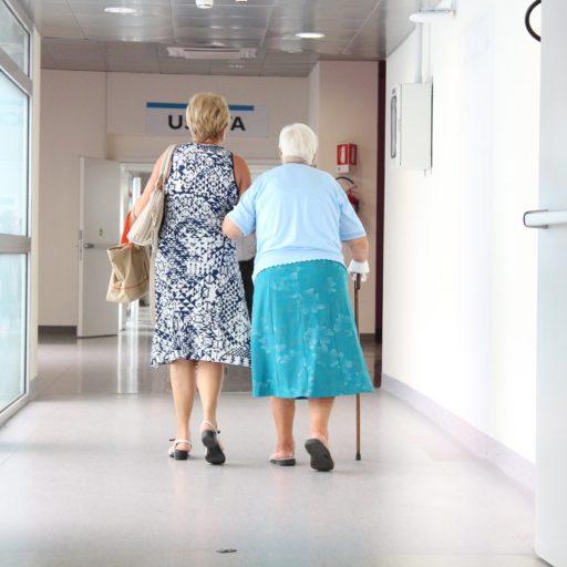 Ältere Frau mit Gehstock stützt sich auf jüngere Frau, von hinten
