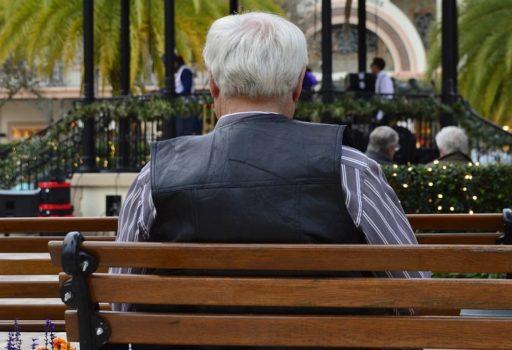 Älterer Mann auf einer Bank, von hinten.