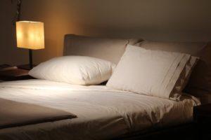 Doppelbett, daneben brennt eine Nachttischlampe.