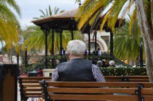 Älterer Mann sitzt auf einer Bank, von hinten.