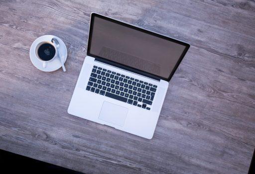 Laptop, daneben eine Kaffeetasse.