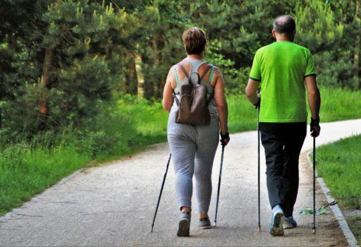 Ein Mann und eine Frau beim Walken, von hinten.