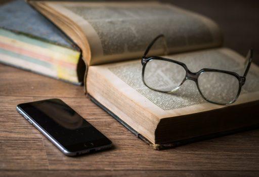 Aufgeschlagenes Buch, darauf eine Brille und daneben ein Smartphone.
