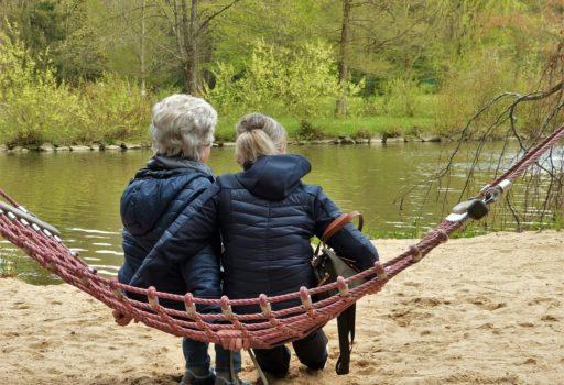 Zwei Frauen sitzen auf einer Hängematte an einem See, von hinten.