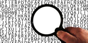 Symbolbild: Lupe über Buchstaben, die Buchstaben sind nur außerhalb der Lupe zu sehen.