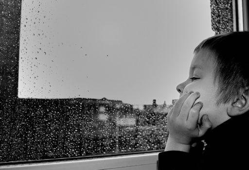 Junge sieht traurig aus einem Fenster.