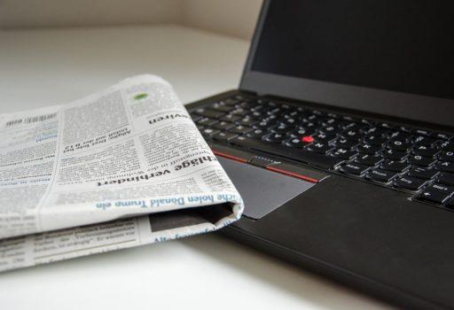 Zeitung liegt auf Laptop