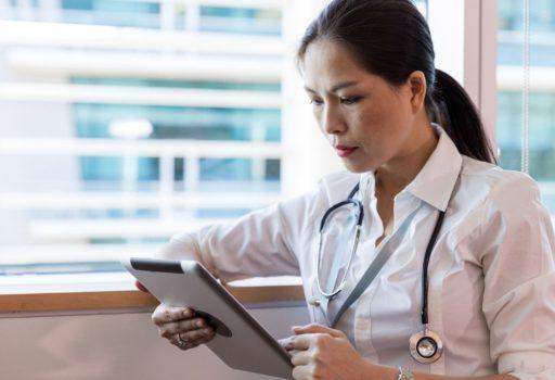 Ärztin hält ein Tablet in der Hand.
