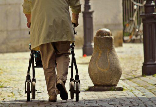Älterer Mann mit Rollator, von hinten.