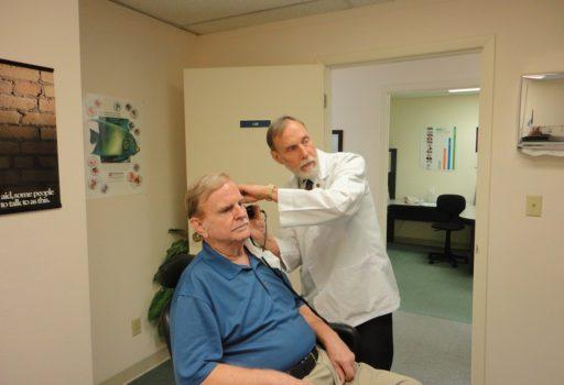 HNO-Arut untersucht einen älteren Mann.