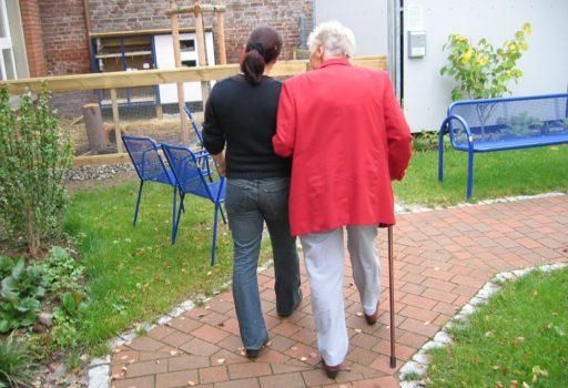 Junge Frau stützt ältere Frau, von hinten.