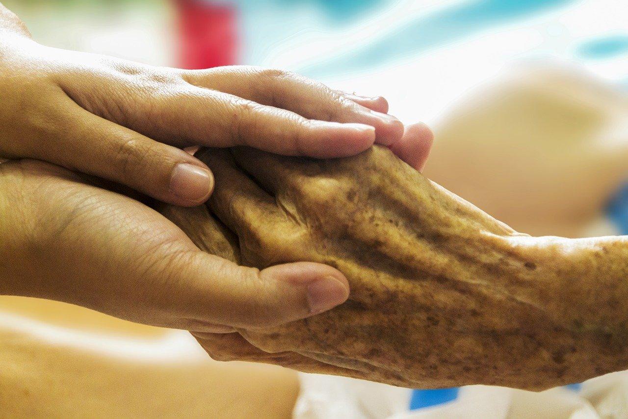 Jüngere Hände halten eine ältere.