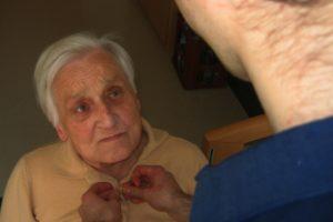 Ältere Frau erhält Hilfe beim Anziehen.