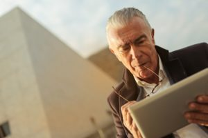 Älterer Mann benutzt ein Tablet.