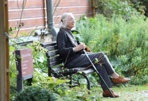 Ältere Frau sitzt draußen auf einer Bank.