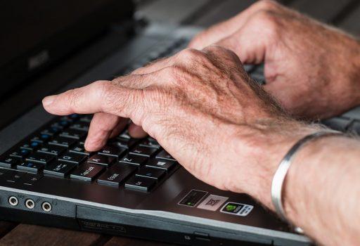 Hände eines älteren Mannes auf einer Tastatur