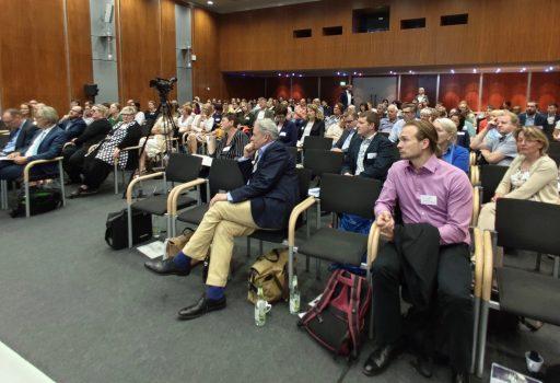 Gäste sitzen bei der Auftaktveranstaltung von digiDEM Bayern im Saal
